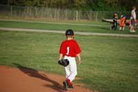 Little League player walking off field representing baseball ends