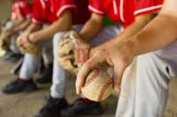 Baseball players sitting on bench representing NCAA D1 baseball colleges